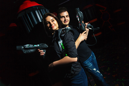 Dark room girl and funny guy playing laser tag
